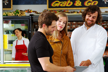 Butcher and couple reviewing various options of meats