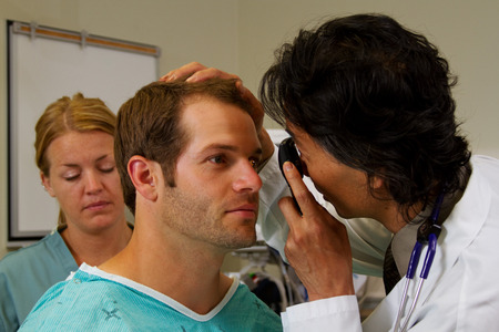 eye disease: Doctor checking patients eyes in emergency department Stock Photo
