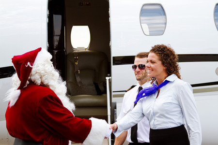 Santa Claus being greeted as he enter airplane