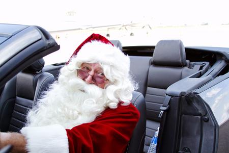 man driving: Santa driving a blue convertible