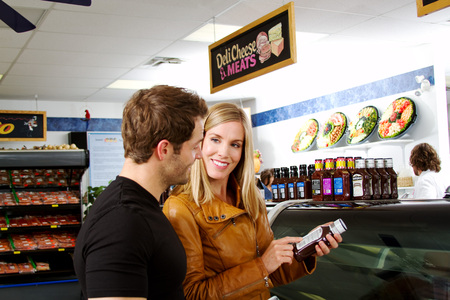 Couple checking labels in butcher shop