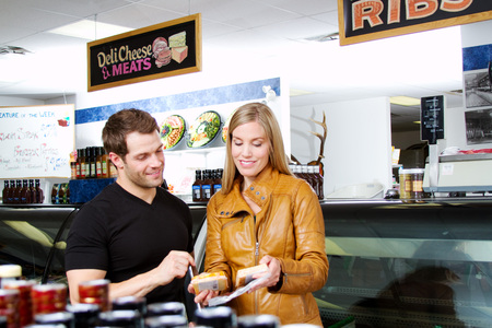 Couple in butcher shop checking out cheeses