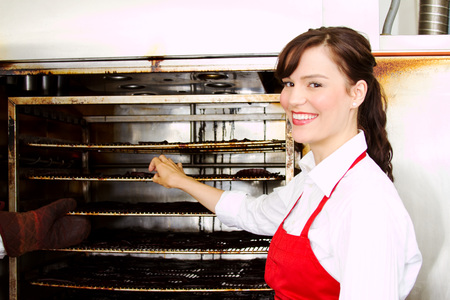 Female employee in butcher shop checking smoked meats Stok Fotoğraf