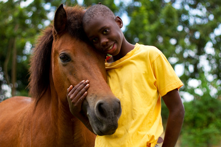 Boy and horse giving each other a hug Stock Photo