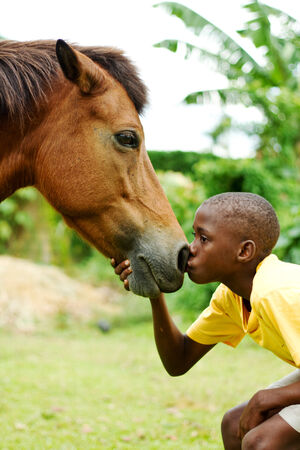 Boy giving his horse a kiss