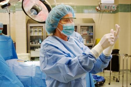 Nurse adjusting her surgical gloves in operating room