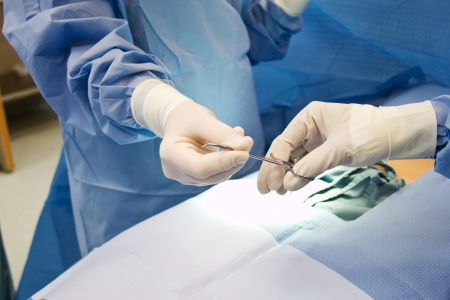 operation gown: Enfermera dando instrumento m�dico durante la operaci�n