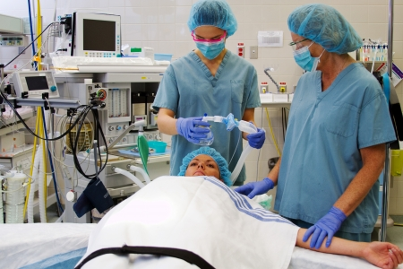 operating: Staff and patient in operating room preparing for anesthetic