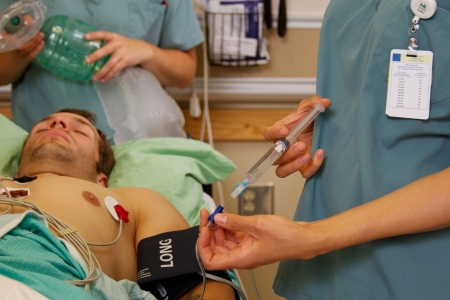 Nurse giving intravenous medication photo