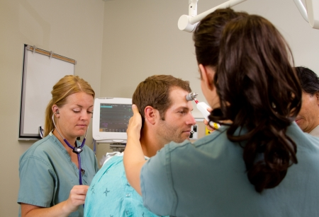 assessing: Health team assessing patient in emergency department Stock Photo