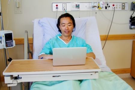 Convalescing patient looking at computer  Stock Photo