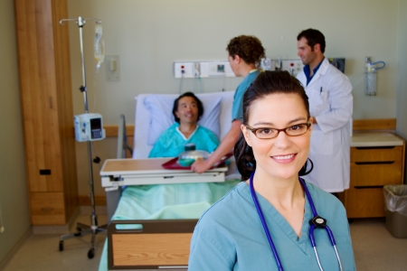 Nurse in patients room with other team members in background photo