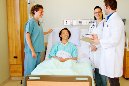 Doctors and nurse with patient in his room