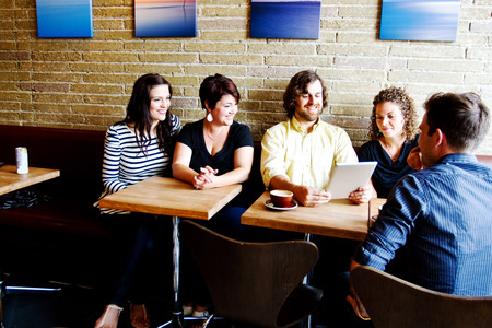 Group of young adults at coffee shop looking at tablet photo
