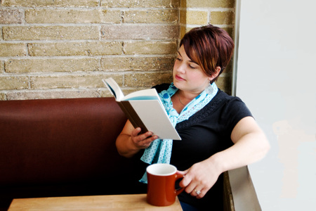book shop: Young woman reading book in coffee shop