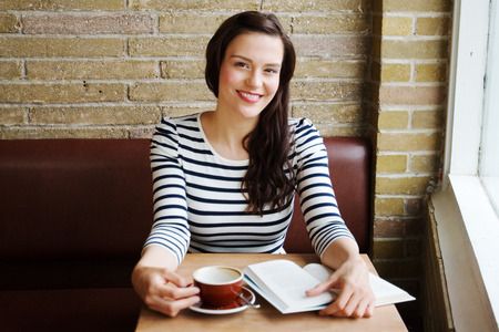 Young woman reading from book in coffee shop Stock Photo