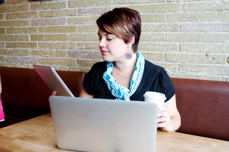 Young woman in coffee shop using tablet and computer photo