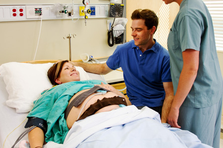 maternity ward: Husband and wife on maternity ward in hospital with nurse overlooking