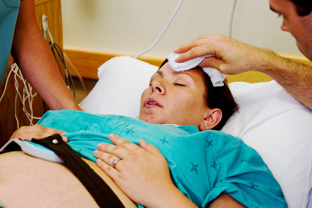 Pregnant Mom in labor with husband and nurse at bedside