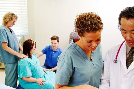 Doctor and nurse reviewing reports of maternity patient photo