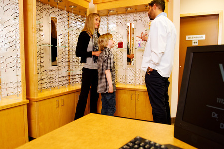 Mom and child in optometry office looking for glasses photo