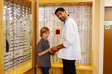 Optometrist showing glasses to young lad at clinic photo