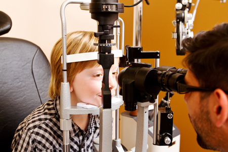 Optometrist checking childs eyes and vision Stock Photo