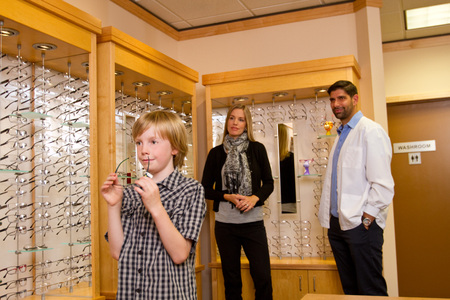 Young boy trying on glasses in optometry office photo