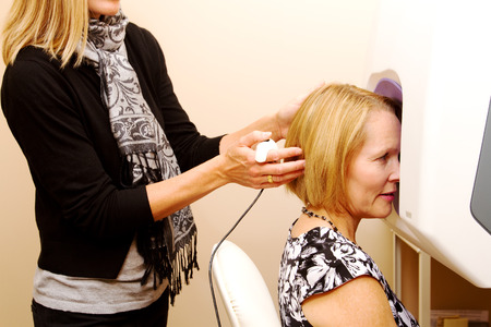 obtain: Optician assisting patient to obtain correct positioning for test Stock Photo
