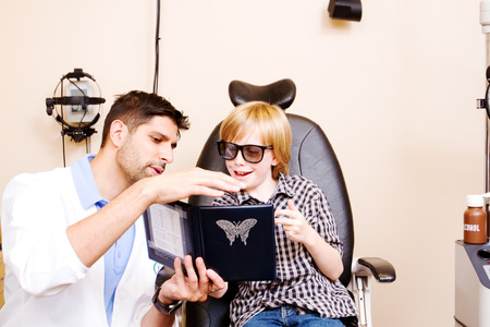 Optometrist testing child in clinic for depth perception Stock Photo