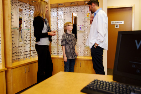 Child trying on glasses in optometry office photo