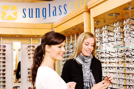 Optician assisting lady in choosing glasses