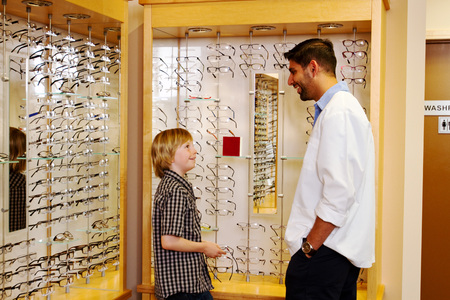 Young lad checking out glasses in clinic Reklamní fotografie