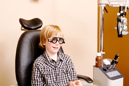 Youth with specialized glasses at optometrist clinic photo