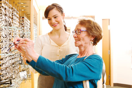 Optician assiting older lady with her choice of glasses