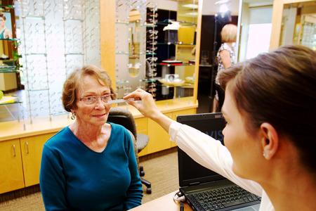 Optician doing eye measurements on senior Standard-Bild