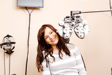 Young woman looking around optical equipment in office
