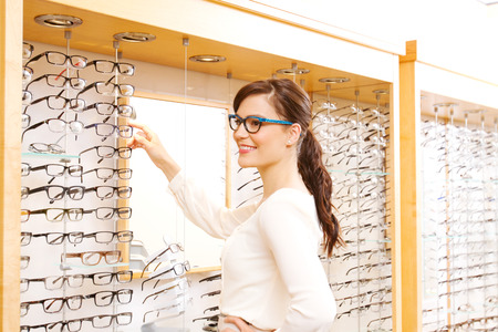 Young woman checking out options for glasses Stock Photo
