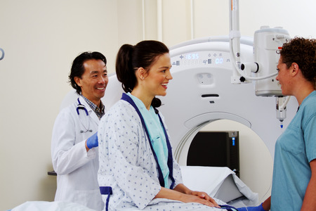 Physician, technician and patient conversing concerning ultrasound Stock Photo