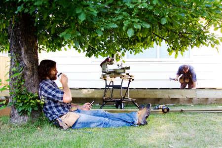 obrero: Carpintero disfruta de un café en la sombra del árbol