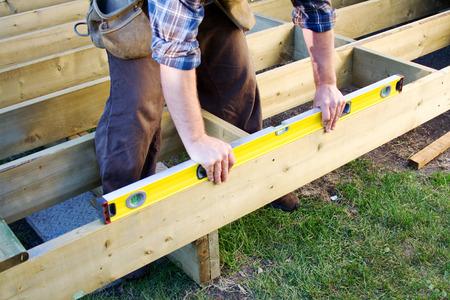 Carpenter checking level of deck boards