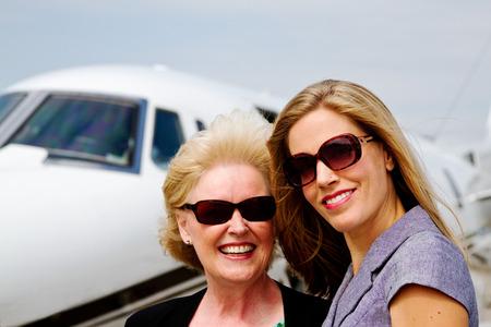 Two women standing near jet plane Standard-Bild