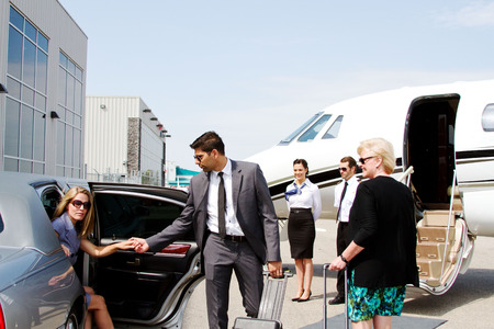 Chauffeur: lady stepping out of limo with help of chauffeur Stock Photo