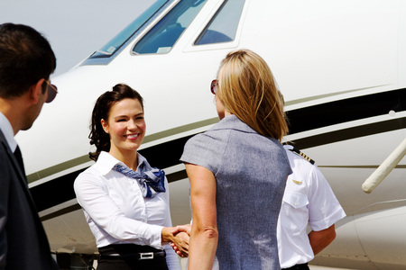 greets: Flight crew greeting passenger prior to boarding plane Stock Photo