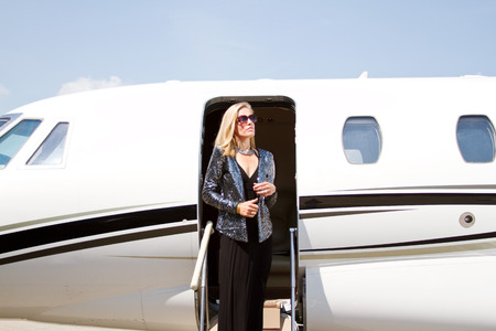 exits: Young lady Diva exits airplane Stock Photo