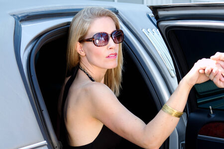 exiting: Diva lady having assistance exiting vehicle Stock Photo