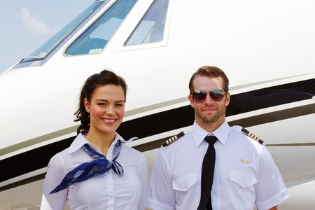 Pilot and stewardess standing by plane ready for passengers