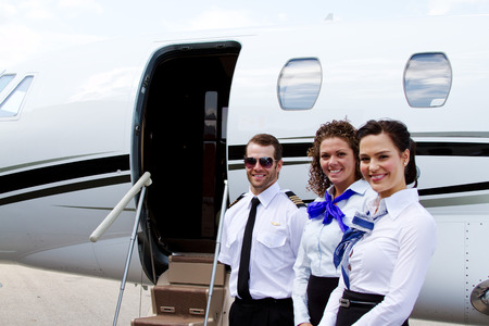 Pilot and stewardesses standing by jet