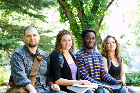 Group of University students sitting on bench outside