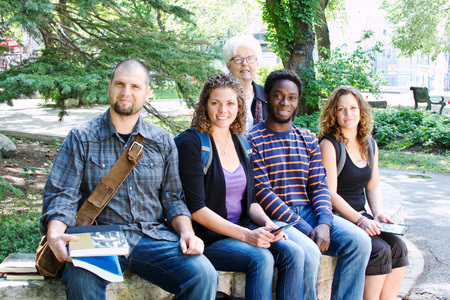 college professor: Four students sitting on bench with instructor standing behind them